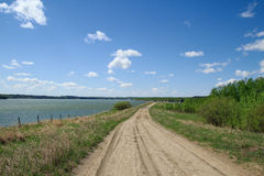Gravel road beside lake Stock Images
