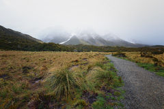 Gravel road leading to snow capped mountain which covered by thick fog. Royalty Free Stock Photos
