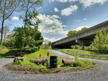 Gravel Road Loops to a Parking Lot Adjacent to a Bridge. It's a beautiful, sunny day in Laurys Station, Pennsylvania, USA. Nature lovers can use this road to Royalty Free Stock Photo