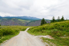 Gravel road in a mountain valley at the top of the Altai Mountains Summer Royalty Free Stock Photos