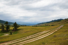 Gravel road in a mountain valley at the top of the Altai Mountains Stock Photo