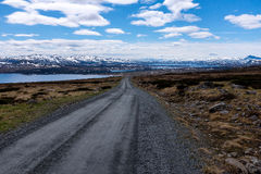 Gravel Road in Norway. With snowy mountains in background Stock Photo