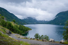 Gravel road at norwegian beautiful fjord shore. Gravel serpentine road at scenic norwegian fjord shore. Mountains and clouds - typical Norway landscape Stock Photo