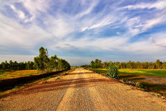 Gravel road pass the green field. With blue sky Stock Photo