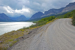 Gravel road runs along river and mountains in Glacier National Park. Stock Images