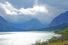 Gravel road runs along river and mountains in Glacier National Park. Royalty Free Stock Photo
