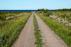 Gravel road straight to the sea Stock Photo