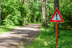 Gravel road in summer countryside. Gravel road in sunny summer countryside with perspective and bright red attention sign Stock Photography
