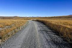 Gravel road to the mountains Royalty Free Stock Photo