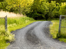 Gravel road to nowhere. In a field with link fence Royalty Free Stock Photos