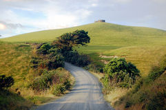 Gravel road turn left at rural area near water tank on hill top. Dargaville, New Zealand stock images