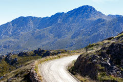 Gravel road up the mountains Stock Photos