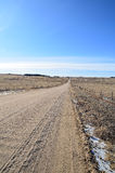 Gravel road in winter. A gravel road heads straight towards the horizon, crossing winter fields in the high plains of Colorado Stock Photo