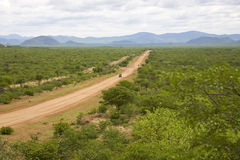 Gravel road with 4x4 car driving and the Zebra mountains, Namibi Stock Images
