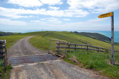 Gravel road with yellow sign in farmland Stock Image