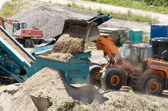 Gravel screening. Loader poured a portion of the sand sifter Royalty Free Stock Photography