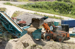 Gravel screening. Loader poured a portion of the sand sifter Royalty Free Stock Photo