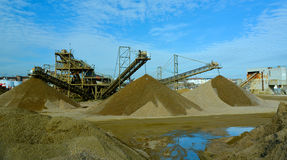 Gravel and stone quarry piles and machinery. Working gravel, stone and sand quarry royalty free stock photography