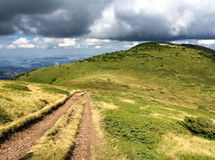 Gravel track across mountains with dramatic clouds. Gravel track across mountains with dramatic stormy cumulonimbus clouds low on the summit in a scenic royalty free stock photos