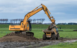 Gravel Transporting. Digger and a tip truck transporting gravel across a muddy Paddock Royalty Free Stock Photos