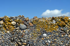 Gravel wall with blue sky. Weathered colorful gravel concrete wall against a blue sky Royalty Free Stock Photography