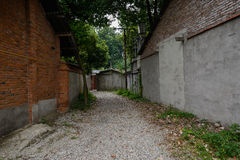 Gravel way between aged red-brick buildings Stock Photos