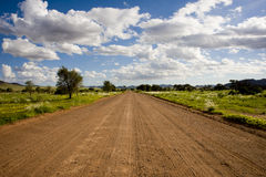 Dirt road in Namibia. Fresh raked graveled road in the south of Namibia, Africa, near Maltahöhe, with blooming meadows beside Stock Images