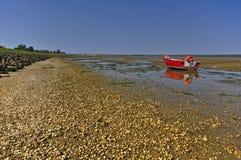 Gravelez la plage avec le bateau de pêche et les mudflats de marée images stock