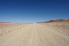 Gravelez la route dans le désert Photographie stock libre de droits