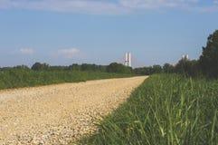 Gravelez la route un matin ensoleillé avec le pont en avant photographie stock