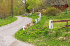 Gravelled countryroad, Sweden. Gravelled countryroad with a red house in Sweden during summer Stock Photos