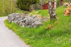 Gravelled countryroad, Sweden. Side of an gravelled countryroad with a red house in Sweden during summer Royalty Free Stock Photos