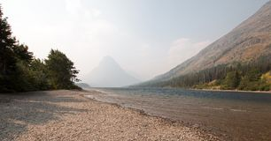 Gravelly shoreline of Upper Two Medicines Lake in Glacier National Park during the 2017 fall forest fires in Montana USA. Gravelly shoreline of Upper Two stock photo