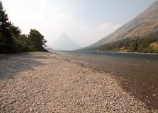 Gravelly shoreline of Upper Two Medicines Lake in Glacier National Park during the 2017 fall forest fires in Montana USA stock image
