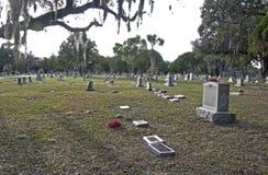Graven en tumbstones bij een begraafplaats Stock Fotografie