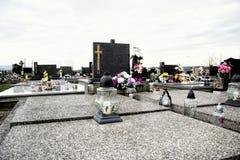 Graven, grafstenen en kruisbeelden op traditionele begraafplaats Votive kaarsenlantaarn en bloemen op grafstenen in kerkhof stock foto