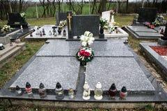 Graven, grafstenen en kruisbeelden op traditionele begraafplaats Votive kaarsenlantaarn en bloemen op grafstenen in kerkhof stock foto's