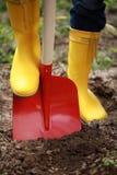 Gravende grond met een schop Stock Afbeeldingen