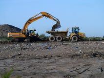 Graver en kipwagenvrachtwagen die aan de terugwinning van de afvalgrond werken Stock Foto's