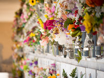 Graves with flowers on a wall of a European cemetery. Stock Images