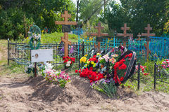 Graves, flowers, wreaths and crosses in cemetery Stock Photography