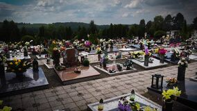 Graves with many flowers in the cemetery Hungary/Europe. Marble tombstone granite monument headstone, artificial flowers.