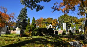 Graves of Notre-Dame-des-Neiges Cemetery. MONTREAL CANADA OCTOBER 11 2015: Graves of Notre-Dame-des-Neiges Cemetery with colorful autumn trees. Is the largest royalty free stock photos