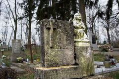 Graves, tombstones and crucifixes on traditional cemetery. Statue of an angel on old tomb stone in graveyard. All Saints' Day Royalty Free Stock Image