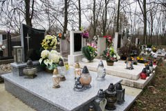 Graves, tombstones and crucifixes on traditional cemetery. Votive candles lantern and flowers on tomb stones in graveyard Royalty Free Stock Photo
