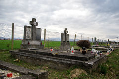 Graves, tombstones and crucifixes on traditional cemetery. Votive candles lantern and flowers on tomb stones in graveyard Stock Photography