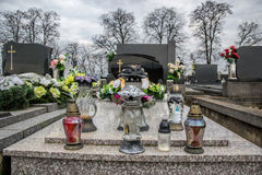 Graves, tombstones and crucifixes on traditional cemetery. Votive candles lantern and flowers on tomb stones in graveyard Royalty Free Stock Images
