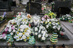 Graves, tombstones and crucifixes on traditional cemetery. Votive candles lantern and flowers on tomb stones in graveyard Stock Photos