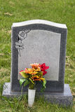Gravestone. Blank granite gravestone with summer flowers in front. A rose design is in the top left corner Stock Images