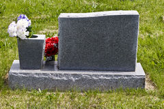 Gravestone. Blank granite gravestone with flowers on the side Royalty Free Stock Image